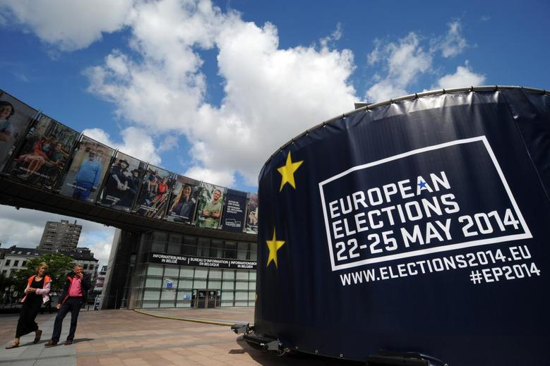 People walk in front of visuals promoting the European elections in front of the European Parliament in Brussels May 24, 2014. REUTERS/Eric Vidal