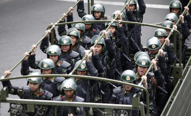 Paramilitary policemen stand on a truck as they travel along a street during an anti-terrorism oath-taking rally in Urumqi, Xinjiang Uighur Autonomous Region May 23, 2014. REUTERS/Stringer