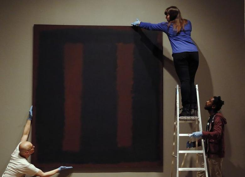 Tate staff pose with the restored Mark Rothko artwork ''Black on Maroon, 1958'' at the Tate Modern in London May 13, 2014.  REUTERS/Luke MacGregor
