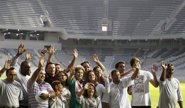 Brazil's President Dilma Rousseff (C) poses with workers as she visits the Arena da Baixada stadium in Curitiba May 9, 2014. REUTERS/Rodolfo Buhrer