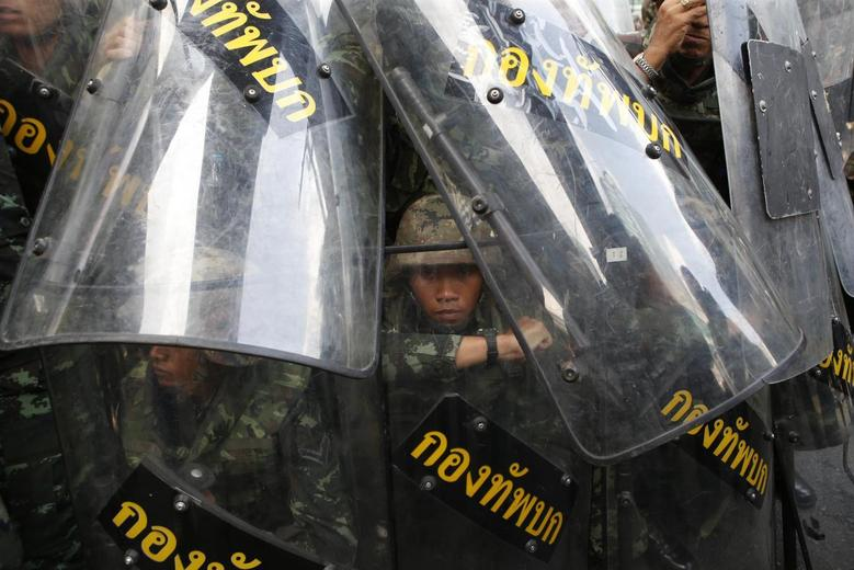 A soldier looks out from behind shields as they take up position to block protestors at a shopping district in central Bangkok May 25, 2014. REUTERS/Erik De Castro