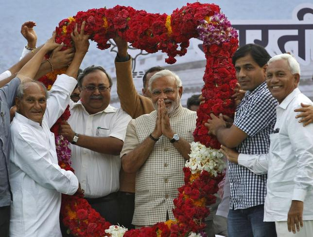 Hindu nationalist Narendra Modi, the prime ministerial candidate for India's main opposition Bharatiya Janata Party (BJP), gestures as he receives a garland from his supporters during a public meeting in Vadodara, in the western Indian state of Gujarat, May 16, 2014. REUTERS/Amit Dave