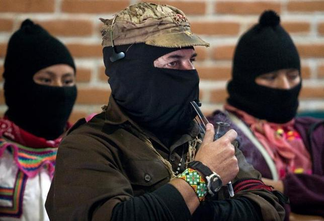 The leader of the Zapatista National Liberation Army (EZLN), Subcomandante Marcos (C) smokes a pipe during opening of the forum to mark the fifteenth anniversary of the Zapatista uprising in San Critobal de las Casas in Mexico's state of Chiapas, January 2, 2009. REUTERS/Jorge Dan Lopez
