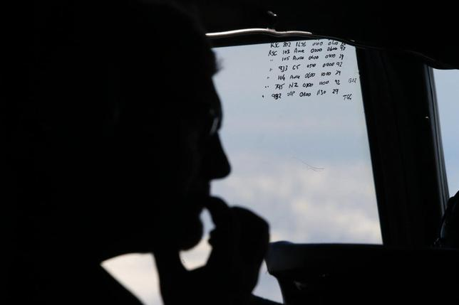 A crew member aboard a Royal New Zealand Air Force P-3K2 Orion aircraft is pictured alongside handwritten notes of other search craft in the area, during a search for the missing Malaysian Airlines flight MH370 over the southern Indian Ocean, March 29, 2014. REUTERS/Jason Reed