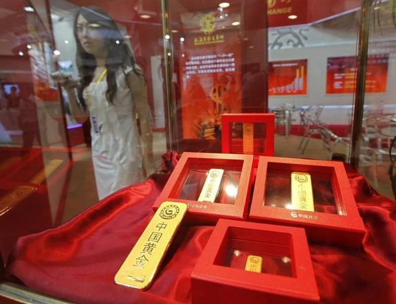 A Shanghai Gold Exchange employee stands beside gold bars displayed at the China International Exhibition on Financial Banking Technology & Equipment in Beijing September 9, 2010. REUTERS/Petar Kujundzic