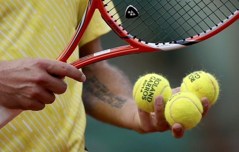 Stanislas Wawrinka of Switzerland checks balls during his men's singles match against Guillermo Garcia-Lopez of Spain at the French Open tennis tournament at the Roland Garros stadium in Paris May 26, 2014.                    REUTERS/Gonzalo Fuentes