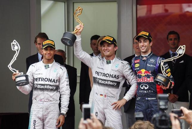 Winner Mercedes Formula One driver Nico Rosberg of Germany, second placed Mercedes Formula One driver Lewis Hamilton (L) of Britain and third placed Red Bull Formula One driver Daniel Ricciardo (R) of Australia react on the podium of the Monaco Grand Prix in Monaco May 25, 2014. REUTERS/Robert Pratta