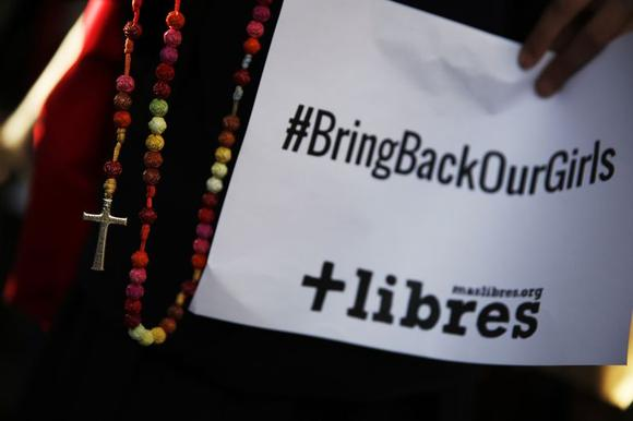 A poster with the Twitter campaign hashtag #BringBackOurGirls is seen during a prayer vigil showing support for Nigerian schoolgirls abducted by militant group Boko Haram, outside the Nigerian Embassy in Madrid May 22, 2014. REUTERS/Susana Vera