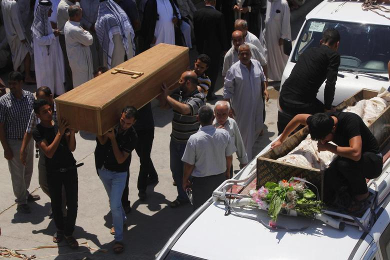 Mourners carry the coffins of victims killed by a suicide bomber attack inside a Shi'ite mosque in Baghdad, during a funeral in Najaf, south of Baghdad, May 28, 2014. REUTERS/ Alaa Al-Marjani