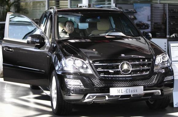 A customer reacts as he inspects the interior of the Mercedes-Benz ML 350 car displayed at a dealership in Beijing February 17, 2012. REUTERS/Jason Lee/Files