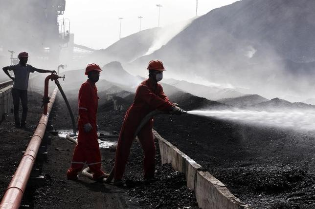 A worker sprays water over piles of coal in Gujarat April 2, 2014. REUTERS/Amit Dave/Files
