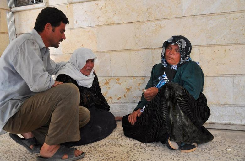A man comforts a woman after activists said people were killed by the Islamic State in Iraq and the Levant (ISIL), in a village near Ras al-Ain city in Hasakah province May 29, 2014. REUTERS/Massoud Mohammed