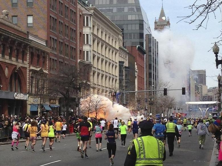 Runners continue to run towards the finish line of the Boston Marathon as an explosion erupts near the finish line of the race in this photo exclusively licensed to Reuters by photographer Dan Lampariello after he took the photo in Boston, Massachusetts, April 15, 2013.  REUTERS/Dan Lampariello
