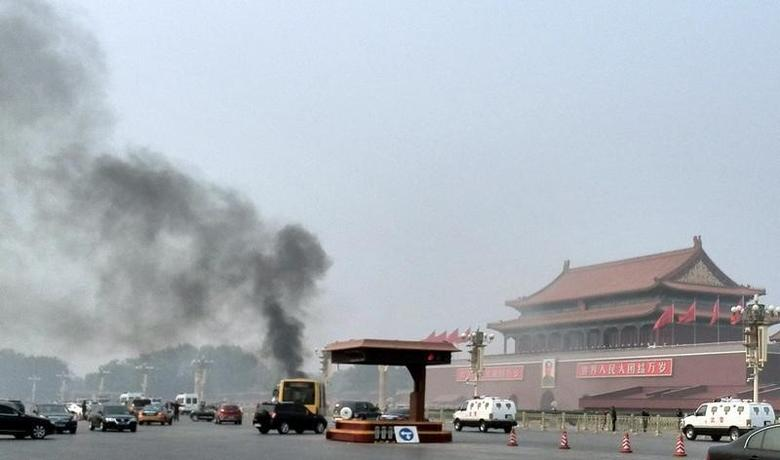 Vehicles travel along Chang'an Avenue as smoke raises in front of a portrait of late Chinese Chairman Mao Zedong at Tiananmen Square in Beijing October 28, 2013.  REUTERS/Staff