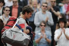 Roger Federer of Switzerland leaves the court after being defeated by Ernests Gulbis of Latvia in their men's singles match at the French Open tennis tournament at the Roland Garros stadium in Paris June 1, 2014.  REUTERS/Stephane Mahe