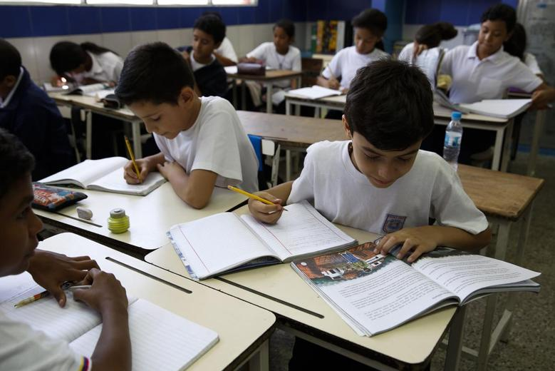 Children read state-issued textbooks from the ''Bicentennial Collection''  at a classroom of the Eleazar Lopez Contreras school in Caracas May 23, 2014. Venezuela's government has published dozens of new textbooks that glorify late president Hugo Chavez and belittle his adversaries, infuriating opposition critics who call them part of a campaign to indoctrinate school children. REUTERS/Carlos Garcia Rawlins