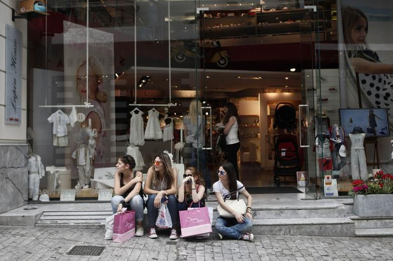 Young women with shopping bags sit outside a shop along the commercial Ermou Street in central Athens May 30, 2014.  REUTERS/Alkis Konstantinidis