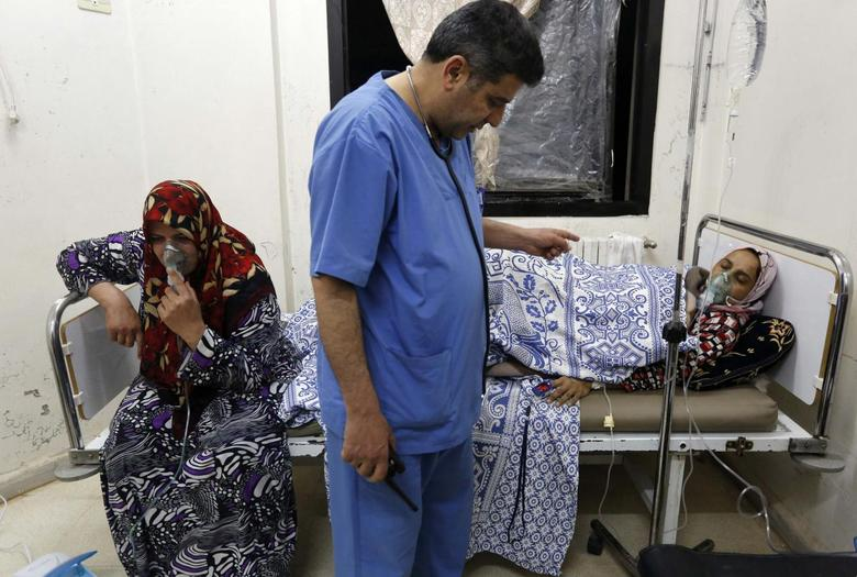 Women, affected by what activists say was a gas attack, receive treatment inside a makeshift hospital in Kfar Zeita village in the central province of Hama May 22, 2014.    REUTERS/Badi Khlif