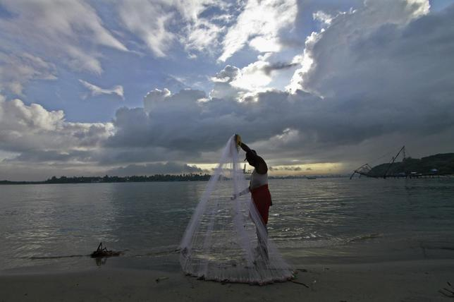 A fisherman arranges his fishing net at a beach against the backdrop of pre-monsoon clouds in Kochi June 5, 2014. REUTERS/Sivaram V