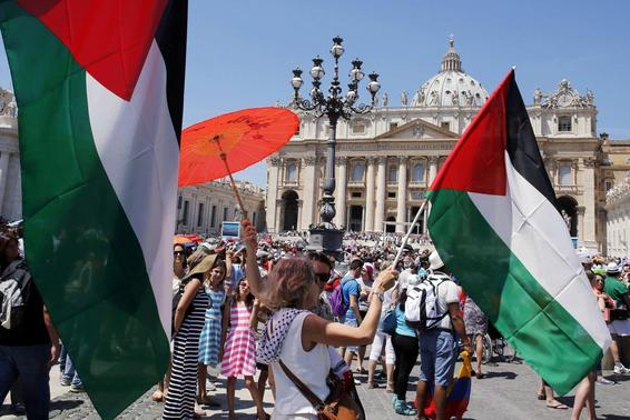 Faithful wave Palestinian flags as Pope Francis delivers his Regina Coeli prayer from the window of the Apostolic Palace in Saint Peter's Square at the Vatican June 8, 2014. REUTERS/Giampiero Sposito
