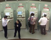 Unas personas en unos cajeros automáticos en Sao Paulo, jun 11 2001. Febraban, el grupo que representa a la industria bancaria en Brasil, dijo que los prestamistas tendrán abiertas sus sucursales durante el horario comercial habitual durante el Mundial, excepto en los días en que juegue la selección nacional.  Reuters/Stringer