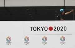 A man works next to host city logos of Tokyo 2020 Bid Committee at an event celebrating Tokyo being chosen to host the 2020 Olympic Games, at Tokyo Metropolitan Government Building in Tokyo September 8, 2013. REUTERS/Yuya Shino