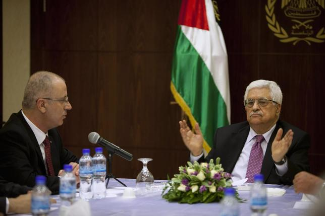 Palestinian President Mahmoud Abbas (R) meets with Palestinian Prime Minister Rami Hamdallah and ministers of the unity government, in the West Bank city of Ramallah June 2, 2014.  REUTERS/Majdi Mohammed/Pool