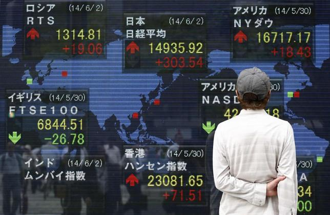 A pedestrian looks at an electronic board showing the stock market indices of various countries outside a brokerage in Tokyo June 2, 2014. REUTERS/Yuya Shino