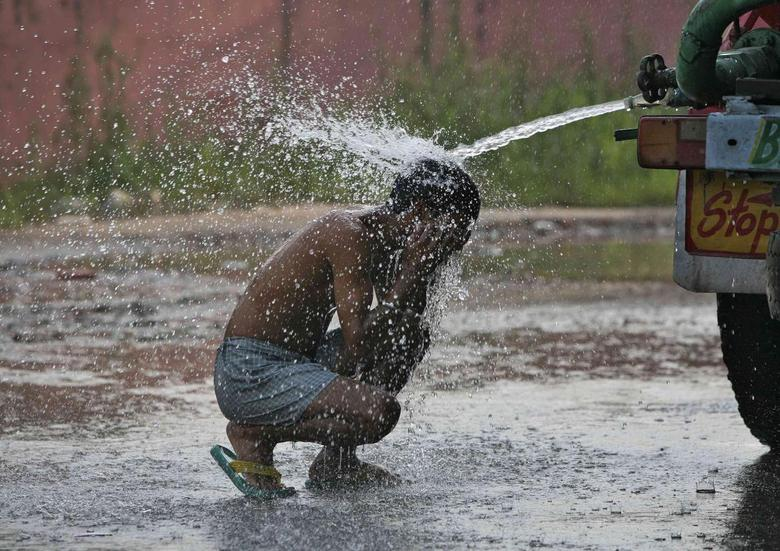 A man bathes while sitting under a water tanker on a hot summer day on the outskirts of Jammu, June 11, 2014.  REUTERS/Mukesh Gupta
