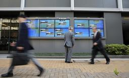 Un hombre mira el promedio del Nikkei japonés y varios valores de otros países afuera de la bolsa de Tokyo, 16 de abril de 2014. El índice Nikkei de Japón cayó el jueves a un mínimo en una semana y media luego de que una revisión a la baja del Banco Mundial de su pronóstico de crecimiento mundial debilitó la confianza.  REUTERS/Toru Hanai