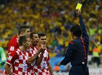 Juiz Yuichi Nishimura mostra cartão amarelho para jogador croata após marcar pênalti a favor do Brasil, na partida inicial da Copa do Mundo, em São Paulo. 12/6/2014 REUTERS/Ivan Alvarado