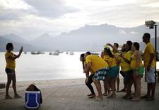 Mulher tira foto de amigos antes de jogo de abertura da Copa do Mundo entre Brasil e Croácia, em Mangaratiba. 12/6/2014 REUTERS/Alessandro Garofalo