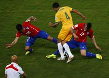 Chile's Charles Aranguiz (L) and Chile's Gary Medel (R) fights for the ball with Australia's Tim Cahill (C) during their 2014 World Cup Group B soccer match at the Pantanal arena in Cuiaba June 13, 2014.  REUTERS/Amr Abdallah Dalsh