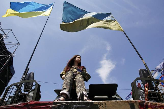 A woman sits on an armoured personnel vehicle during a rally demanding official information from the Ukrainian government on their work in the 100 days since they took power, at Independence Square in Kiev June 8, 2014.   REUTERS/Valentyn Ogirenko