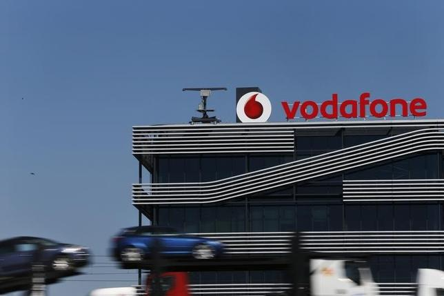 A truck carrying cars speeds past the headquarters of Vodafone in Madrid March 17, 2014.  REUTERS/Susana Vera