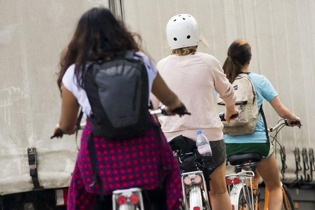 A woman wears a helmet as she cycles on a road in central Berlin, June 17, 2014.  REUTERS/Thomas Peter (GERMANY - Tags: TRANSPORT SOCIETY SPORT CYCLING) - RTR3U90A