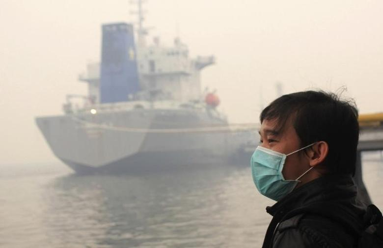 A passenger wearing a mask stands in thick haze as he waits for his ferry heading to Malaysia, in Dumai port, in Indonesia Riau province March 13, 2014. REUTERS/Stringer