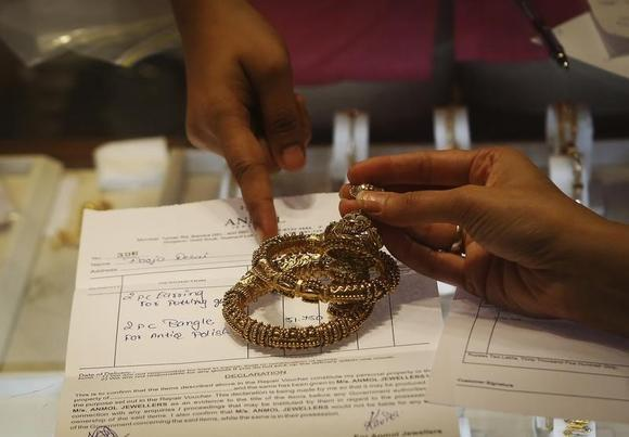 An employee explains the bill to a customer as gold bangles are placed on top of it inside a jewellery showroom in Mumbai August 30, 2013. REUTERS/Danish Siddiqui/Files