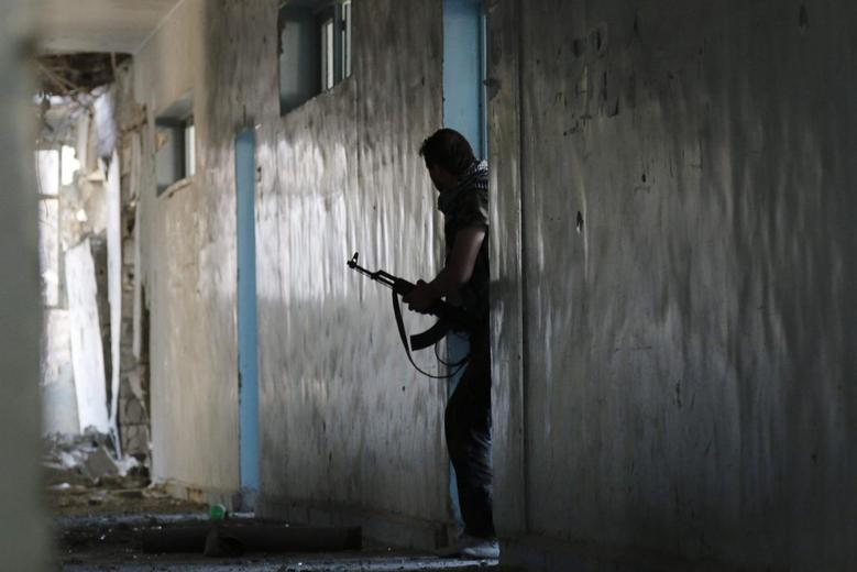 A Free Syrian Army fighter walks with his weapon inside a damaged building on the frontline of Aleppo's Al-Ezaa neighbourhood  June 15, 2014. REUTERS/Hosam Katan