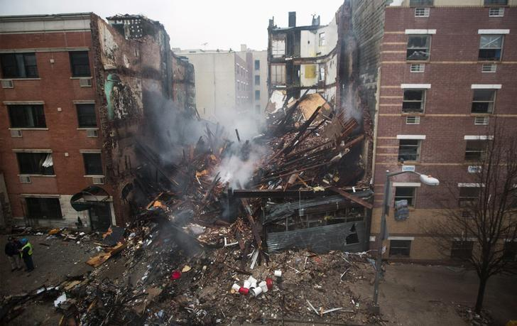 New York City firefighters work at the site of a building explosion and collapse in the Harlem section of New York, March 12, 2014. REUTERS/Brendan McDermid