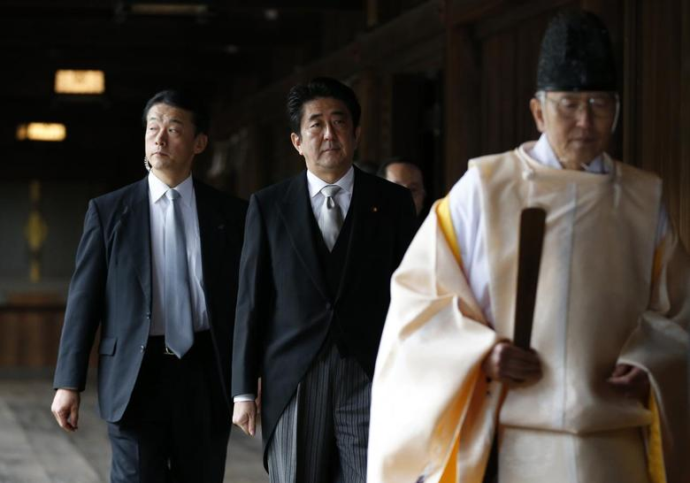 Japan's Prime Minister Shinzo Abe (C) is led by a Shinto priest as he visits Yasukuni shrine in Tokyo in this December 26, 2013 file photo.    REUTERS/Toru Hanai/Files