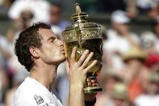 Andy Murray of Britain kisses the winners trophy after defeating Novak Djokovic of Serbia (R) in their men's singles final tennis match at the Wimbledon Tennis Championships, in London July 7, 2013. REUTERS/Anja Niedringhaus/Pool