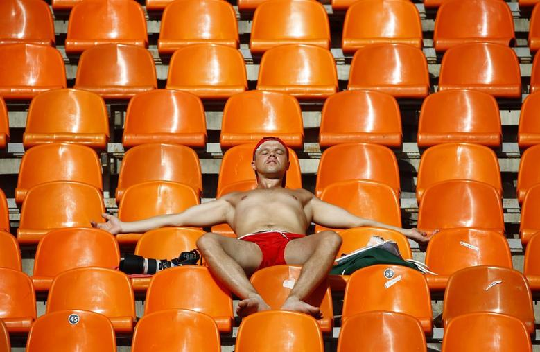 A spectator tans himself in the sun during the IAAF World Athletics Championships in Moscow in this file photo taken August 13, 2013.  REUTERS/Kai Pfaffenbach