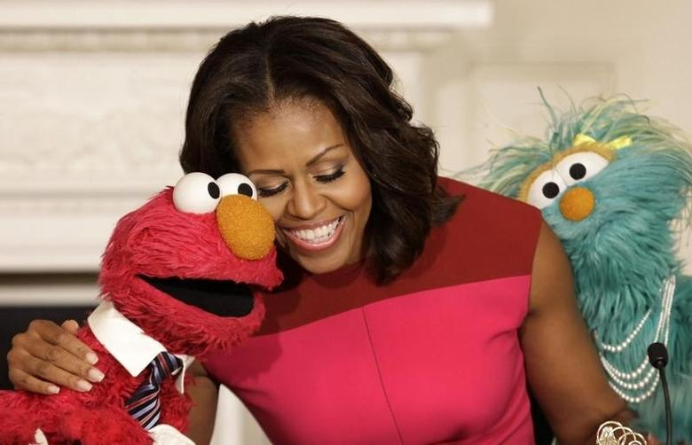 U.S. first lady Michelle Obama hugs PBS Sesame Street characters Elmo and Rosita after delivering remarks on marketing healthier foods to children at the White House in Washington October 30, 2013. REUTERS/Yuri Gripas