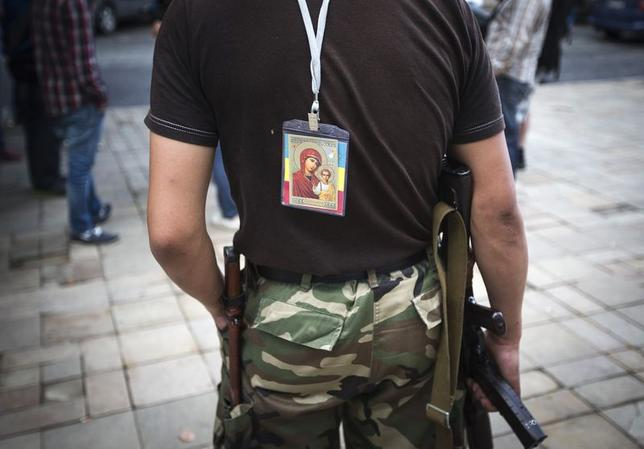 A religious image is hung on a back of an armed pro-Russian separatist guarding the regional administration headquarters in Luhansk June 18, 2014.   REUTERS/Shamil Zhumatov