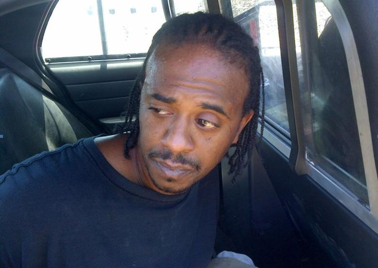 Murder suspect Turhan Robinson is shown in the back of a police car after his capture in this handout photo released by the Jefferson County Sheriff Department June 20, 2014. REUTERS/Jefferson County Sheriff's Office/Handout via Reuters