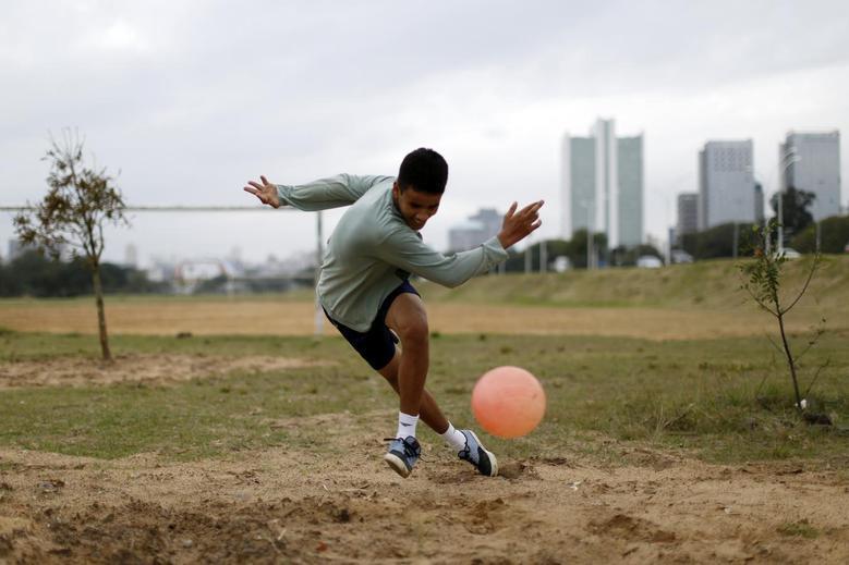 A boy plays soccer in a park in Porto Alegre June 16, 2014. REUTERS/Marko Djurica