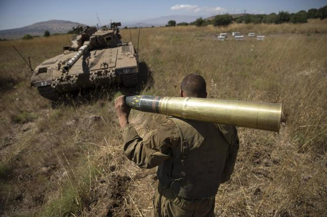 An Israeli soldier carries a tank shell near Alonei Habashan on the Israeli occupied Golan Heights, close to the ceasefire line between Israel and Syria June 22, 2014.  REUTERS/Baz Ratner