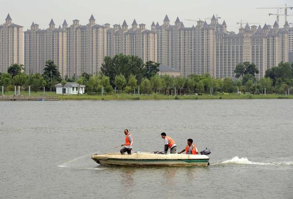 Workers spray chemical into a river to prevent the spread of algae, in front of residential buildings under construction, in Taiyuan, Shanxi province June 18, 2014. REUTERS/Jon Woo