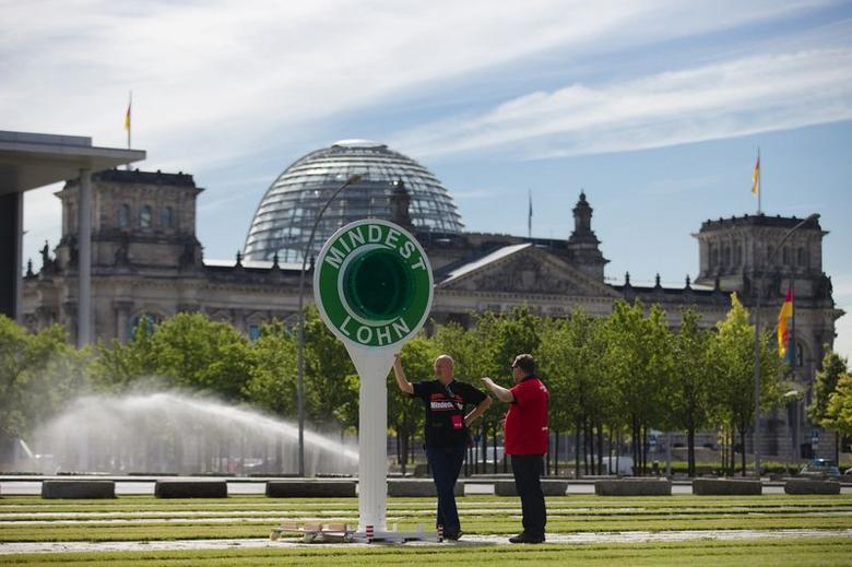 Members of the Verdi trade union stand next to a giant police signalling disc demanding a country wide minimum wage in front of the Reichstag in Berlin, June 18, 2014. The writing reads: ''Minimum Wage''  REUTERS/Thomas Peter (GERMANY - Tags: POLITICS CIVIL UNREST BUSINESS EMPLOYMENT)